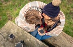 Jong paar onder deken met het hete drank kussen Stock Afbeeldingen