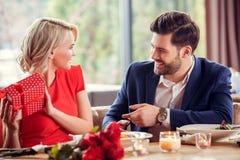 Jong paar op datum in de vrouw die van de restaurantzitting het huidige speels bekijken kerel houden stock afbeeldingen