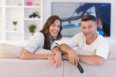 Jong paar op de bank het letten op televisie royalty-vrije stock afbeelding