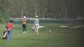 Jong paar op de golfcursus De mensen van de golfcursus groeperen jong het grasgebied van het spelersteam stock footage