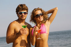Jong paar op de kust met cocktails royalty-vrije stock afbeeldingen