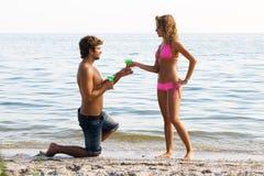 Jong paar op de kust met cocktails stock foto's