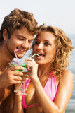 Jong paar op de kust met cocktails Stock Foto