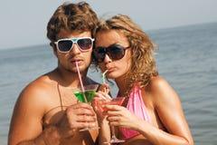 Jong paar op de kust met cocktails Stock Fotografie
