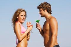 Jong paar op de kust met cocktails Stock Afbeeldingen