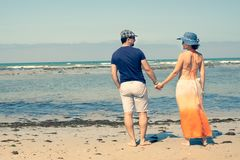 Jong paar op de strandholding elkaar die het overzees bekijken stock foto