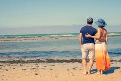 Jong paar op de strandholding elkaar die het overzees bekijken royalty-vrije stock foto's