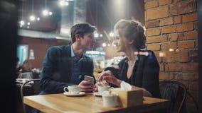 Jong paar op een datum die wat bespreken zij bij smartphone het scherm, het lachen en het kussen zien stock videobeelden