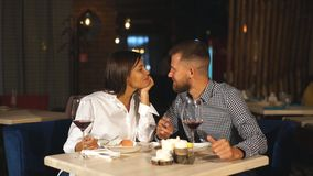 Jong paar op een datum Een man voedt zijn vrouw een heerlijk dessert Paar die in het restaurant lachen stock footage