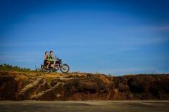 Jong paar op een motorfiets op rotsachtige grond Gelukkig kerel en meisje die op een motor reizen stock fotografie