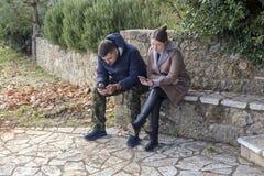Jong paar op het park met telefoons royalty-vrije stock fotografie