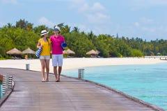 Jong paar op strandpier bij tropisch eiland binnen stock fotografie