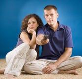 Jong paar op tapijt met afstandsbediening Stock Foto's