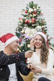 Jong paar in rode hoedenzitting op bank tussen Kerstmisbomen stock foto