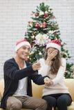 Jong paar in rode hoedenzitting op bank tussen Kerstmisbomen royalty-vrije stock afbeeldingen