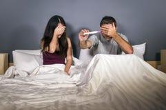 Jong paar samen in zenuwachtig en beklemtoond bed behandelend ogen voor het zien van de holdings geen voorspeller van de zwangers stock afbeelding