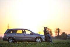 Jong paar, slanke aantrekkelijke vrouw met lange paardestaart en knappe man die zich bij zilveren auto op groen gebied op duideli stock foto