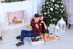 _jong paar stellen op camera, omhelzen elkaar en kussen binnen Royalty-vrije Stock Afbeelding