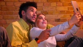 Jong paar van Afrikaanse kerel en Kaukasisch meisje die thuis in videochat op tablet spreken die leuk en grappig zijn stock footage