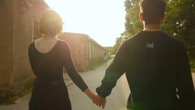 Jong paar van mens en vrouw die op brug bij zomer de lopen Levendige kleuren De modieuze gelukkige handen van de paarholding op d stock video