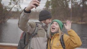 Jong paar van reizigers die selfie terwijl status op een brug tegen de achtergrond van een kleine rivier nemen Jonge mensen stock video