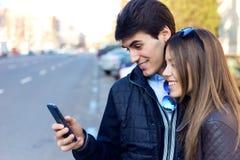Jong paar van toerist in stad die mobiele telefoon met behulp van Stock Fotografie