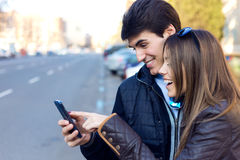 Jong paar van toerist in stad die mobiele telefoon met behulp van Stock Foto's