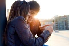 Jong paar van toerist in stad die mobiele telefoon met behulp van Stock Afbeeldingen
