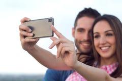 Jong paar van toerist in stad die mobiele telefoon met behulp van Stock Afbeelding