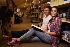 Jong paar van vrolijke studenten die op de vloer zitten en in de universitaire bibliotheek bestuderen Stock Afbeeldingen