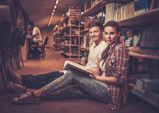 Jong paar van vrolijke studenten die op de vloer zitten en in de universitaire bibliotheek bestuderen Royalty-vrije Stock Afbeelding