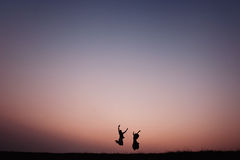 Jong paarsilhouet dat in openlucht bij dramatische zonsondergang springt Stock Fotografie