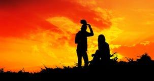 Jong paarsilhouet die zonsondergang kijken royalty-vrije stock foto