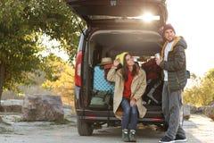 Jong paarverpakking het kamperen materiaal in autoboomstam royalty-vrije stock foto