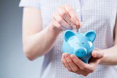 Jong Person Adding Cash aan Besparingen royalty-vrije stock afbeelding