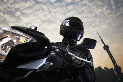 Jong personenvervoer een motorfiets in de loop van de dag, hemel en de bouwbuitenkanten op de achtergrond Royalty-vrije Stock Fotografie