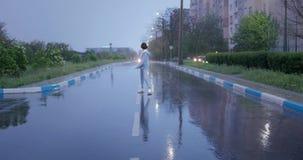Jong positief meisje die, en pret hebben onder regen dansen lopen Slecht weer, natte vreugde, weg, geluk, kort haar stock video