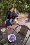 Jong romantisch paar dat dranken op terras heeft Stock Afbeelding
