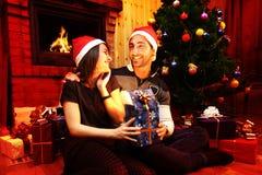 Jong romantisch paar onder de Kerstmisboom thuis met Kerstmisgiften Stock Foto