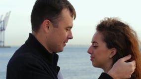 Jong romantisch paar in in slijtage op datum, die van ogenblik van nabijheid op overzees of oceaanachtergrond genieten Vrouw met  stock videobeelden
