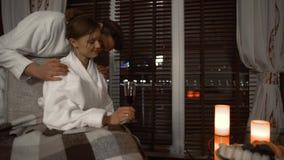 Jong romantisch paar in witte badjassen die in een comfortabele hotelruimte rusten Familievrije tijd stock video