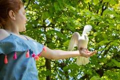 Jong rood haired meisje met een duif in de schaduw van grote groene bladbomen royalty-vrije stock fotografie
