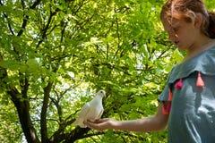 Jong rood haired meisje met een duif in de schaduw van grote groene bladbomen stock afbeelding