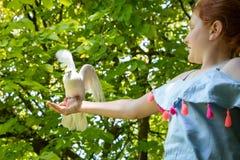 Jong rood haired meisje met een duif in de schaduw van grote groene bladbomen stock fotografie