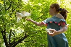 Jong rood haired meisje met een duif in de schaduw van grote groene bladbomen royalty-vrije stock afbeeldingen
