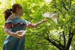 Jong rood haired meisje met een duif in de schaduw van grote groene bladbomen royalty-vrije stock foto