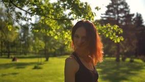 Jong roodharig meisje in bosdraaien rond en kijkend zeer vrolijk en gelukkig stock videobeelden