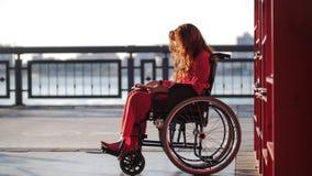 Jong roodharig meisje die een boek in een rolstoel, op de straat lezen royalty-vrije stock fotografie