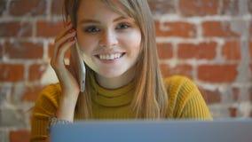 Jong schitterend glimlachend wijfje die op mobiele telefoon spreken en laptop met behulp van stock video