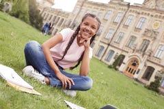 Jong schoolmeisje bij de zitting van de schoolyard op gazon met notitieboekjes en laptop die thuiswerk doen die speelse camera ki royalty-vrije stock afbeelding